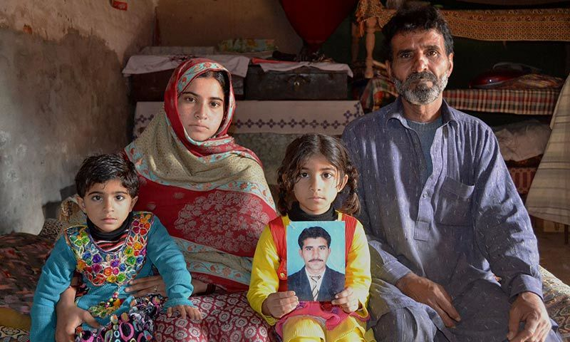 The father of Mohammad Irfan, who was sentenced to death for drug trafficking in Saudi Ariabia, Haji Abdul Haq (R), poses for a photograph with his daughter-in-law and grandchildren in Sargodha. — AFP