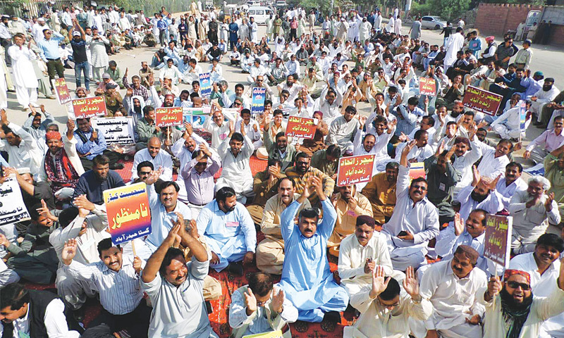 Teachers raise arms during the sit-in against newly-introduced 'education management cadre' here on Wednesday.—Yousuf Nagori