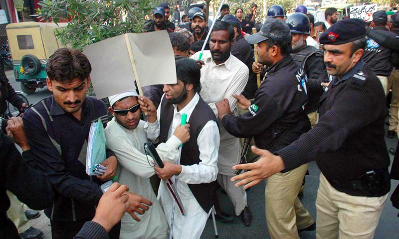 Police pushing visually impaired men as they clear a road during a demonstration in Lahore. —Online