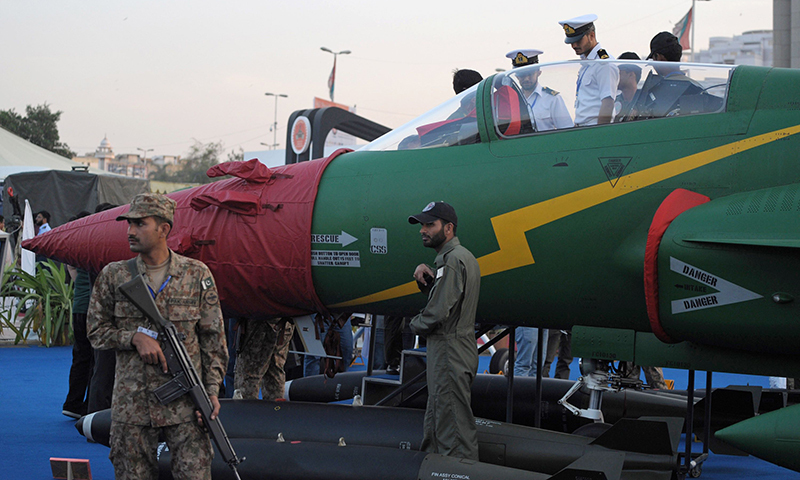A soldier (L) keeps watch as a PAC JF-17 Thunder multirole combat aircraft is pictured on static display at the International Defence Exhibition and seminar (IDEAS) in Karachi. - AFP