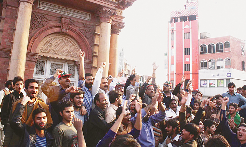 FAISALABAD: Political activists shouting slogans against each other during a face-off at the Clock Tower intersection here on Sunday.—Online