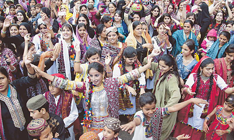 ENTHUSIASTIC people sing and dance to express their joy while celebrating Sindhi culture day at the Karachi Press Club on Sunday.—White Star