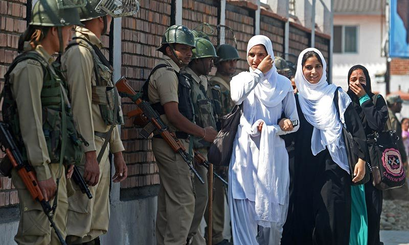 Indian paramilitary troopers stand guard as Kashmiri Muslim school girls walk past outside the state assembly in Srinagar.— AFP/File