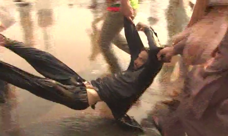 This screengrab from DawnNews shows an injured PTI worker being shifted to a safe location by party workers after being injured in clashes.