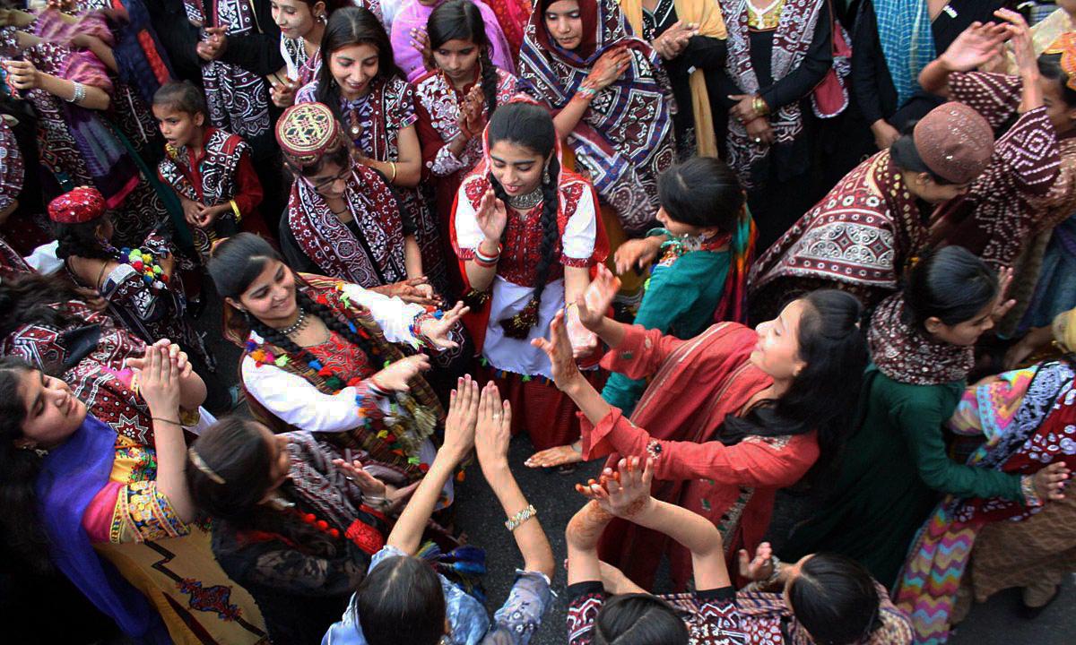 Women dance on traditional Sindhi songs to celebrate Sindhi Topi Ajrak Day outside Karachi Press Club.— ONLINE