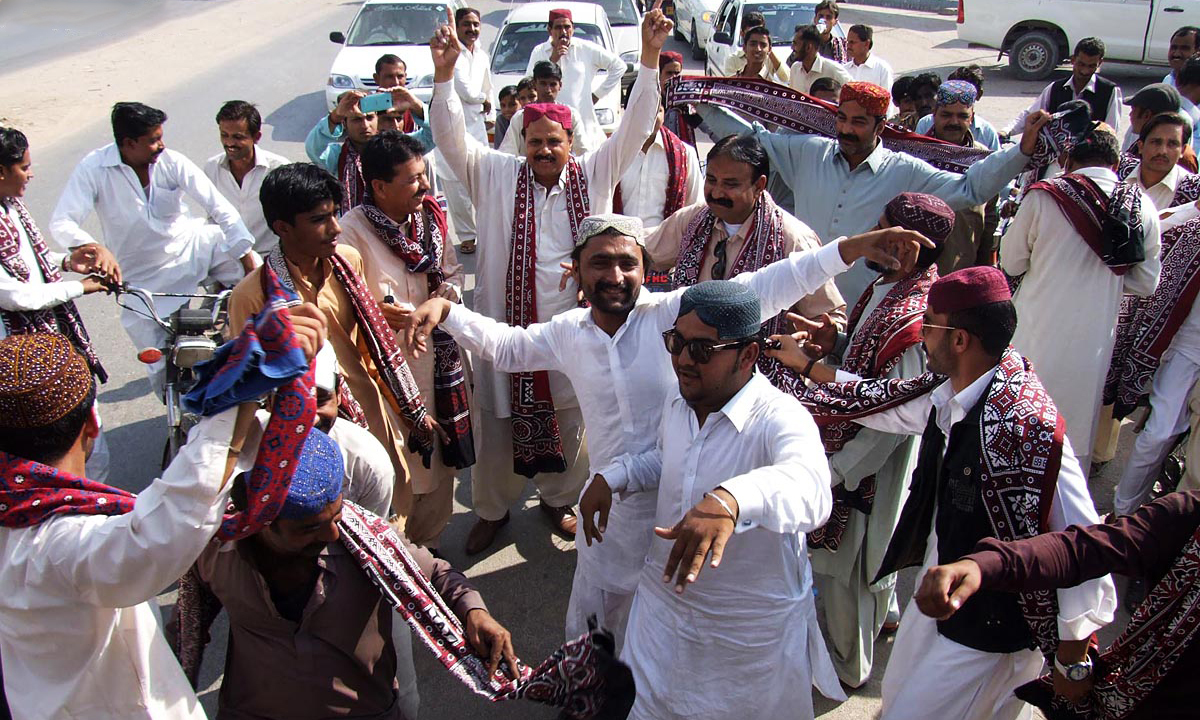 People dance on traditional Sindhi songs on Sindhi Topi Ajrak Day. — ONLINE