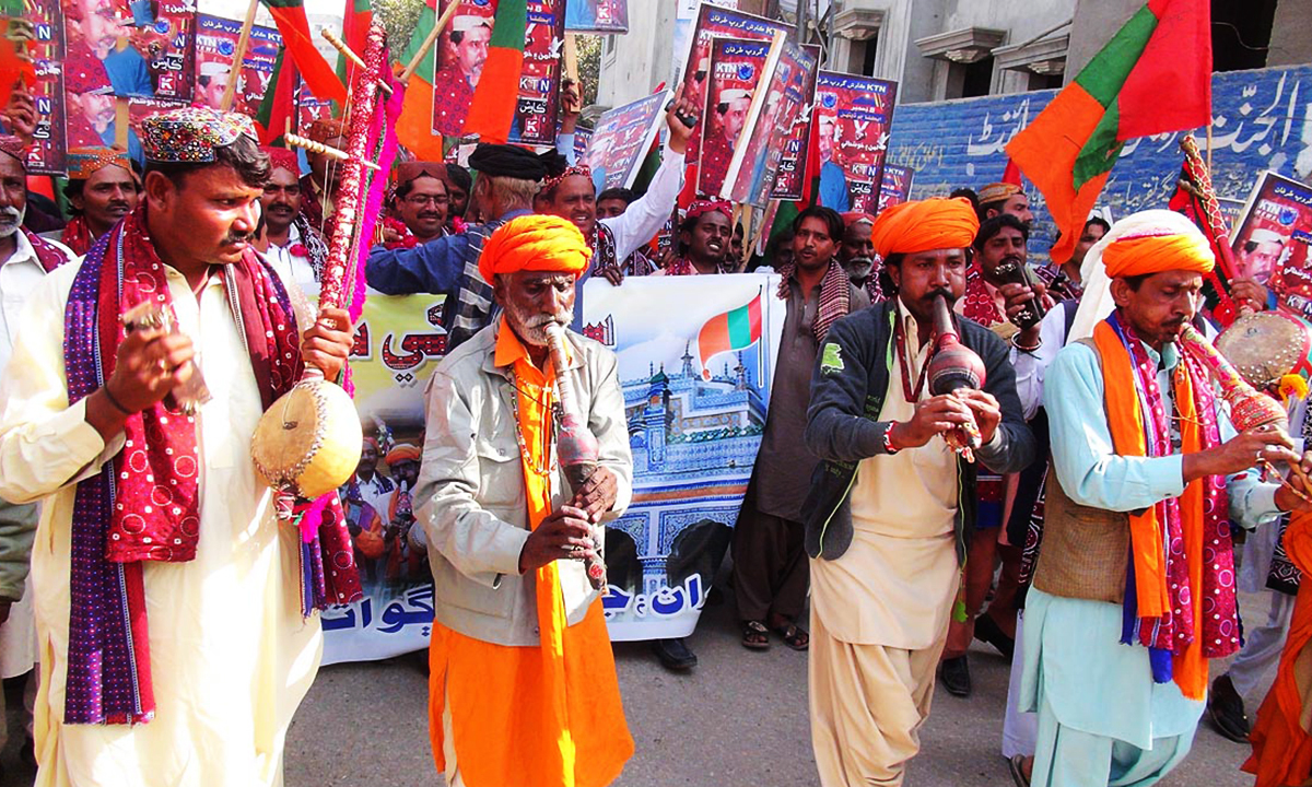 Snake charmers take part in a rally on Sindhi Topi Ajrak Day. —ONLINE