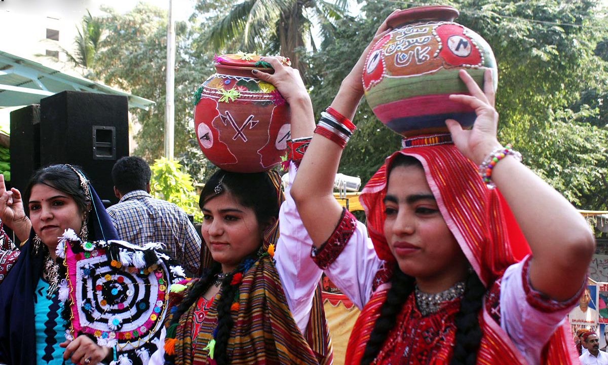 Girls in traditional Sindhi dresses, present a tableau during a ceremony outside Karachi Press Club. — ONLINE