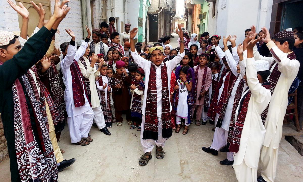 Children wear traditional Ajrak and Sindhi caps.— ONLINE