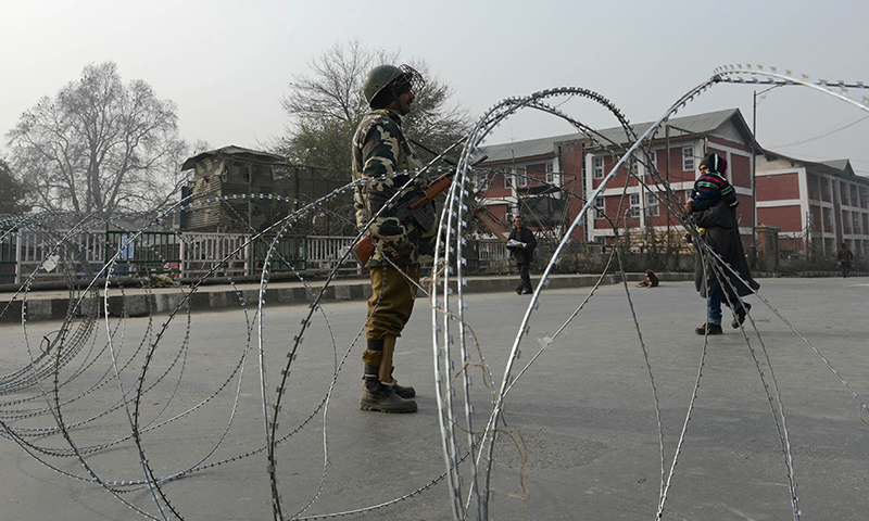 An Indian paramilitary soldier stands guard on a deserted street during a curfew in Srinagar. — AFP