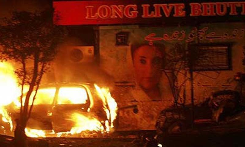 File photo shows site of Karsaz blast on October 18, 2007. A car burning next to a truck which had carried former prime minister Benazir Bhutto during her welcome rally in Karachi.Reuters/File