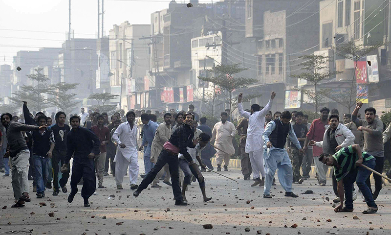 In this photo, activists from Pakistan Tehreek-i-Insaaf throw stones during clashes with ruling party supporters during a protest in Faisalabad on December 8, 2014. — AFP