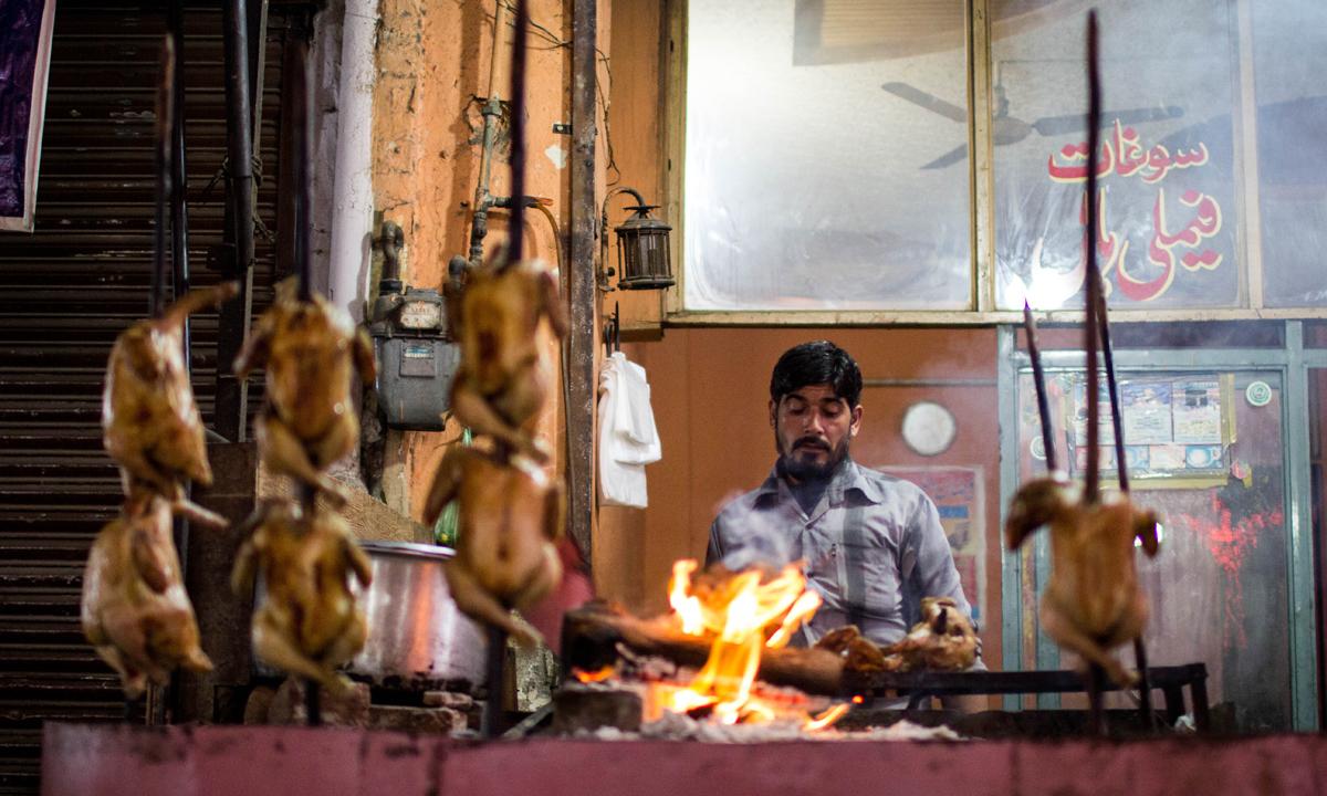 A vendor prepares chicken Sajji. — Photo by Muhammad Umar