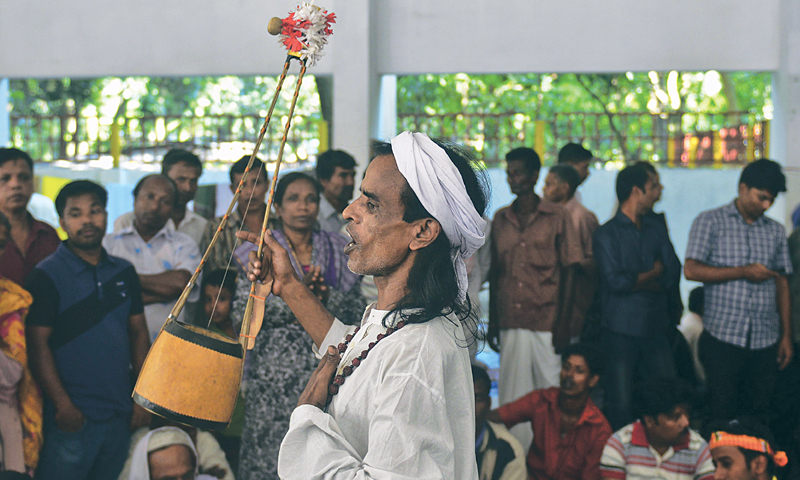 AFTAB and Saleha blindfolded and wearing shrouds with their hands tied, are led to circumbulate the shrine of one of Bangladesh's revered poets and Sufi mendicants in Chheuria village some 250kms from Dhaka. A Baul or minstrel (right) sings at the shrine.—AFP