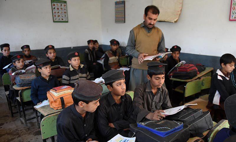 Schoolchildren attend class at a school in Peshawar. — AFP