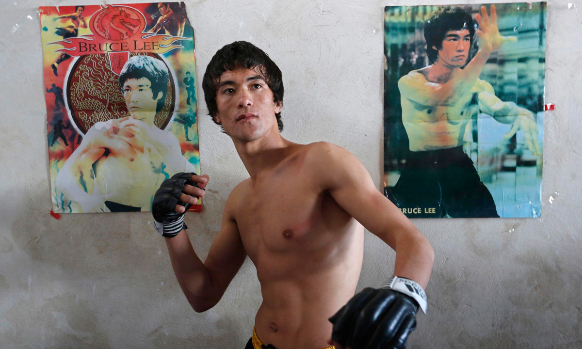 Abbas Alizada, who calls himself the Afghan Bruce Lee, poses for a picture in front of Bruce Lee posters after exercising