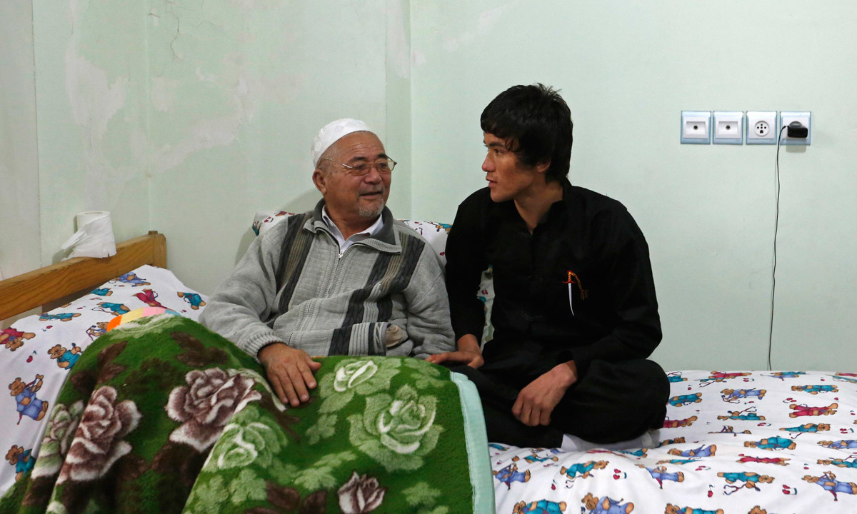 Afghan Bruce Lee (R), talks to his father at their house in Kabul