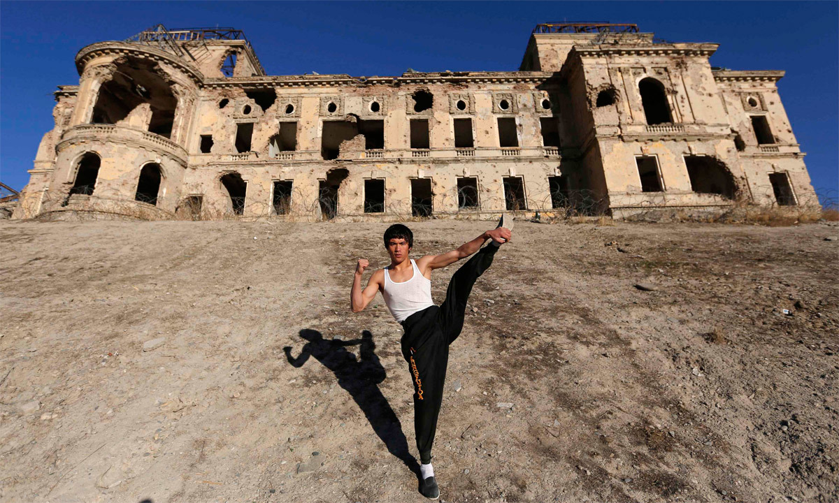Abbas Alizada, who calls himself the Afghan Bruce Lee, poses for the media in front of the destroyed Darul Aman Palace in Kabul