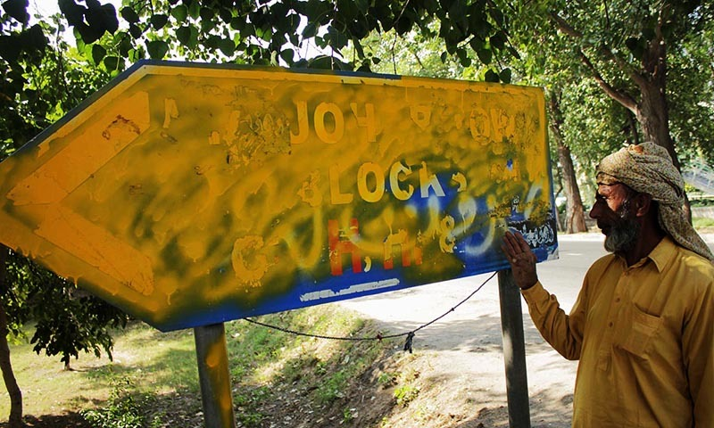 A man showing the sign board where IS graffiti was recently removed, on Lahore's Canal Road. — Online