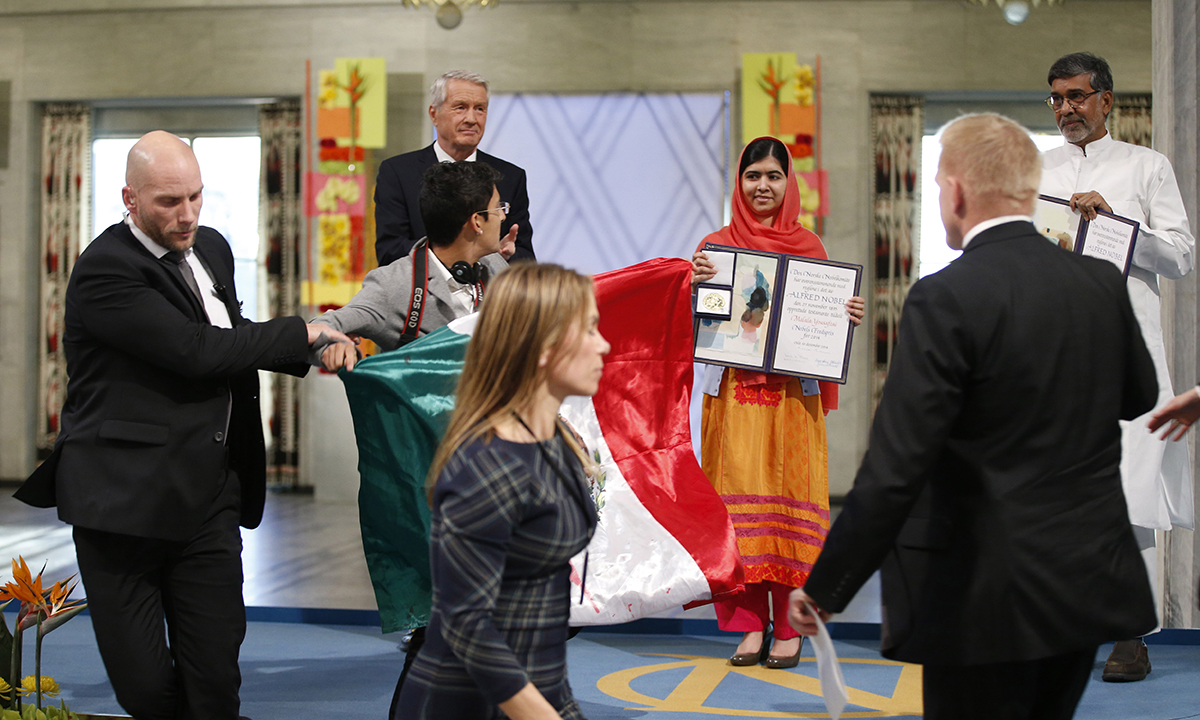 A man holding the Mexican flag is led away by security after attempting to get on stage with Nobel Peace Prize winners Malala Yousafzai and Kailash Satyarthi—AP