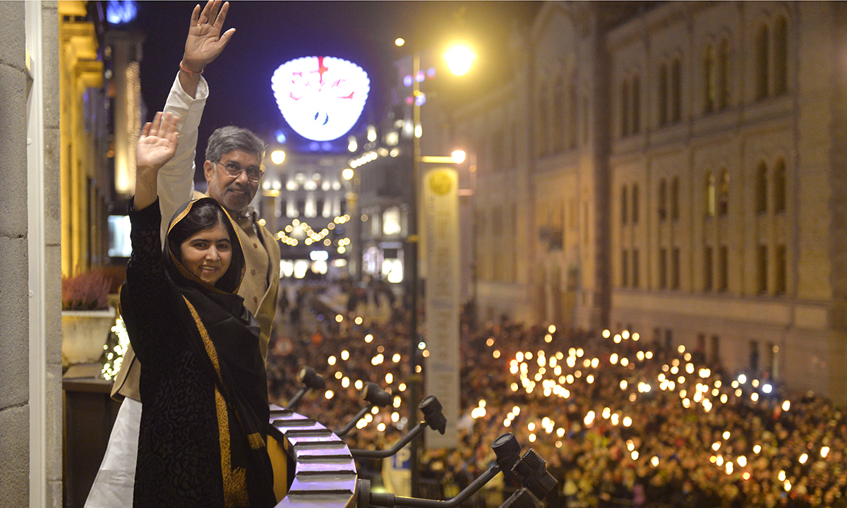 A torchlight procession passes below in honour of the 2014 Nobel Peace Prize laureates Malala Yousafzai, front left, and Kailash Satyarthi, as the laureates wave from the balcony to acknowledge the crowd. . — AP