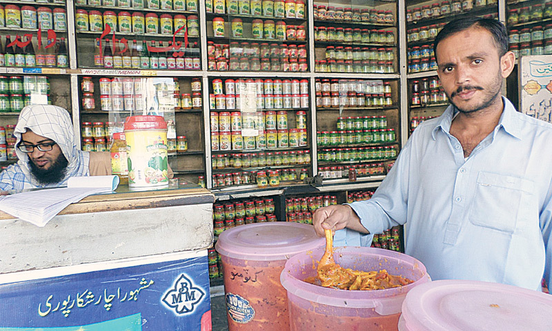 A salesman displays different varieties of achaar at a shop.—Photo by writer