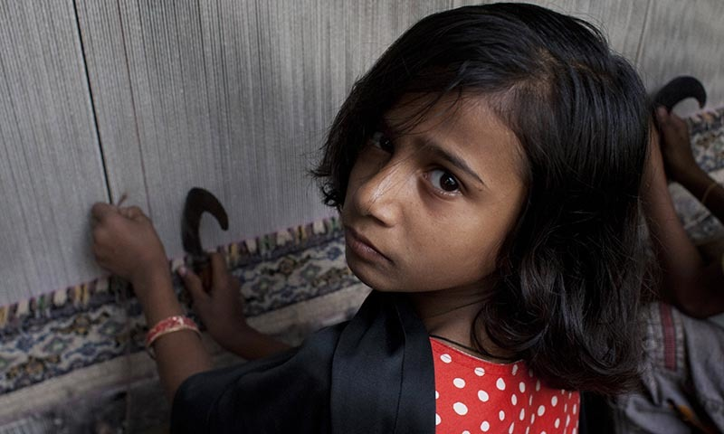 In this Nov. 20, 2014 photo, 8-year-old Fizza weaves carpet in Karachi slums in Pakistan.— AP