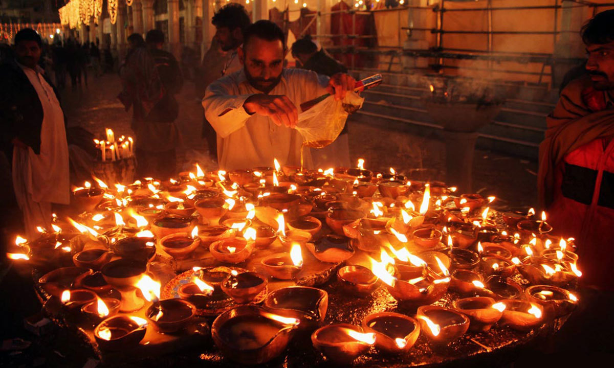 Man pours oil in clay lamps at the shrine of Data Ganj Bakhsh, which is decorated with lights - Online
