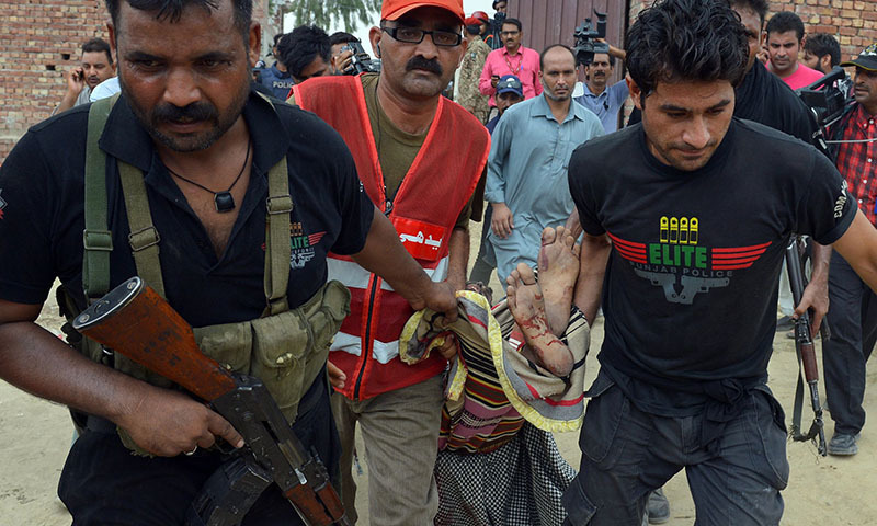 Police commandos carry the body of a suspected militantin Punjab. — AFP/file