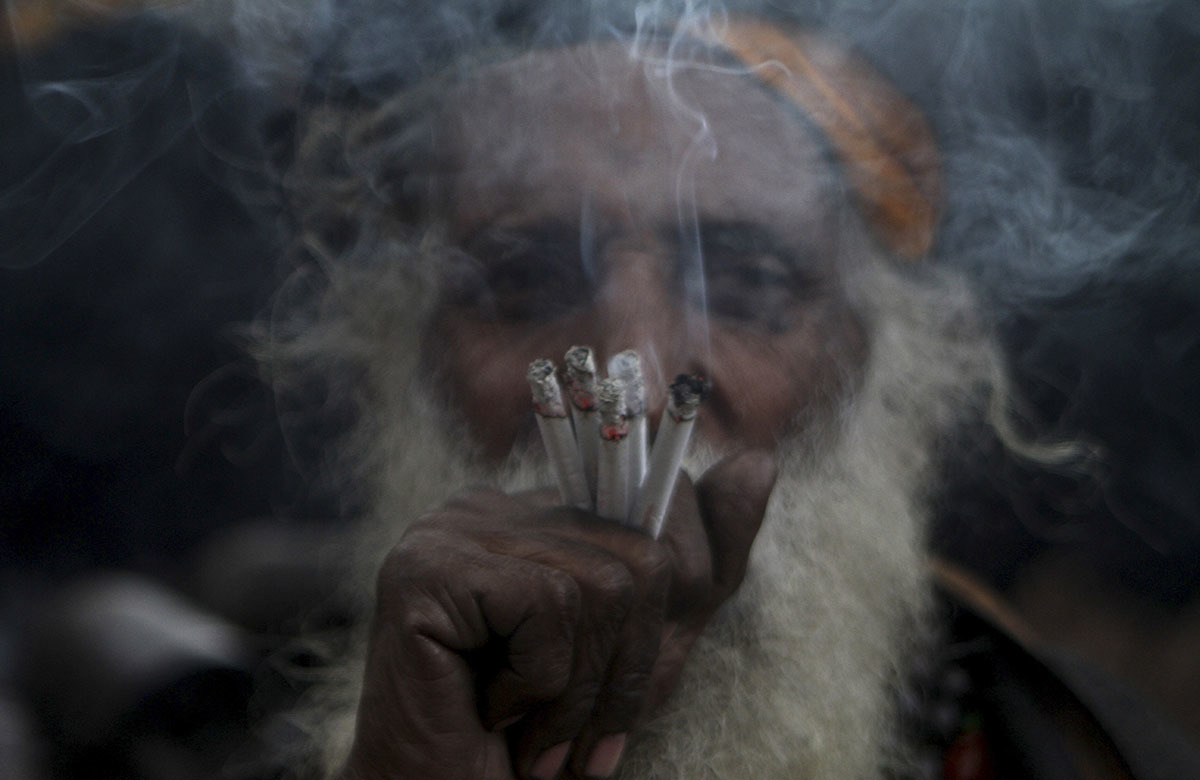 A devotee smokes during the celebrations of the three-day annual congregation at the shrine of Data Ganjbaksh at his shrine. - AP