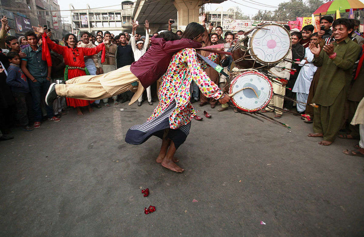 A devotee whirls as he beats drums while another hangs from his back to balance their weight, at the shrine of Sufi Saint Data Ganj Bakhsh in Lahore. - Reuters