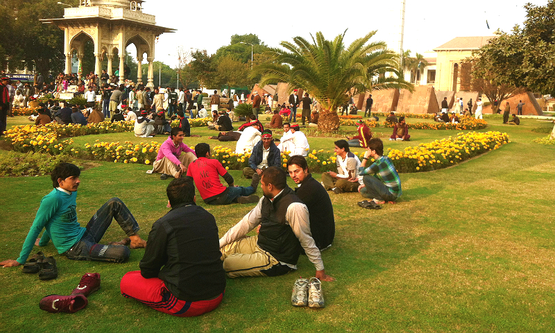 تحریک انصاف کے کارکنان اپنے رہنما کے انتظار میں مال روڈ پر واقع باغ میں انتظار کر رہے ہیں اور عقب میں پنجاب اسمبلی بھی دیکھی جا سکتی ہے۔