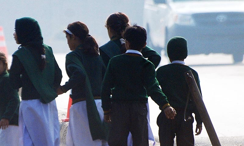 Schoolchildren cross a road as they move away from a military run school that is under attack - Reuters