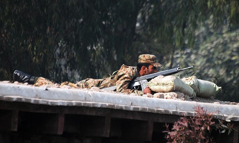 A soldier takes up a position above a road near the military run school that is under attack - Reuters