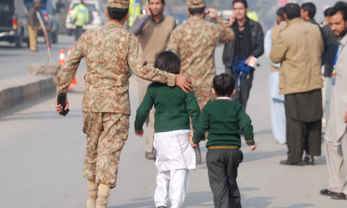 A soldier escorts schoolchildren after they were rescued from the Army Public School that is under attack by Taliban gunmen in Peshawar. — Reuters