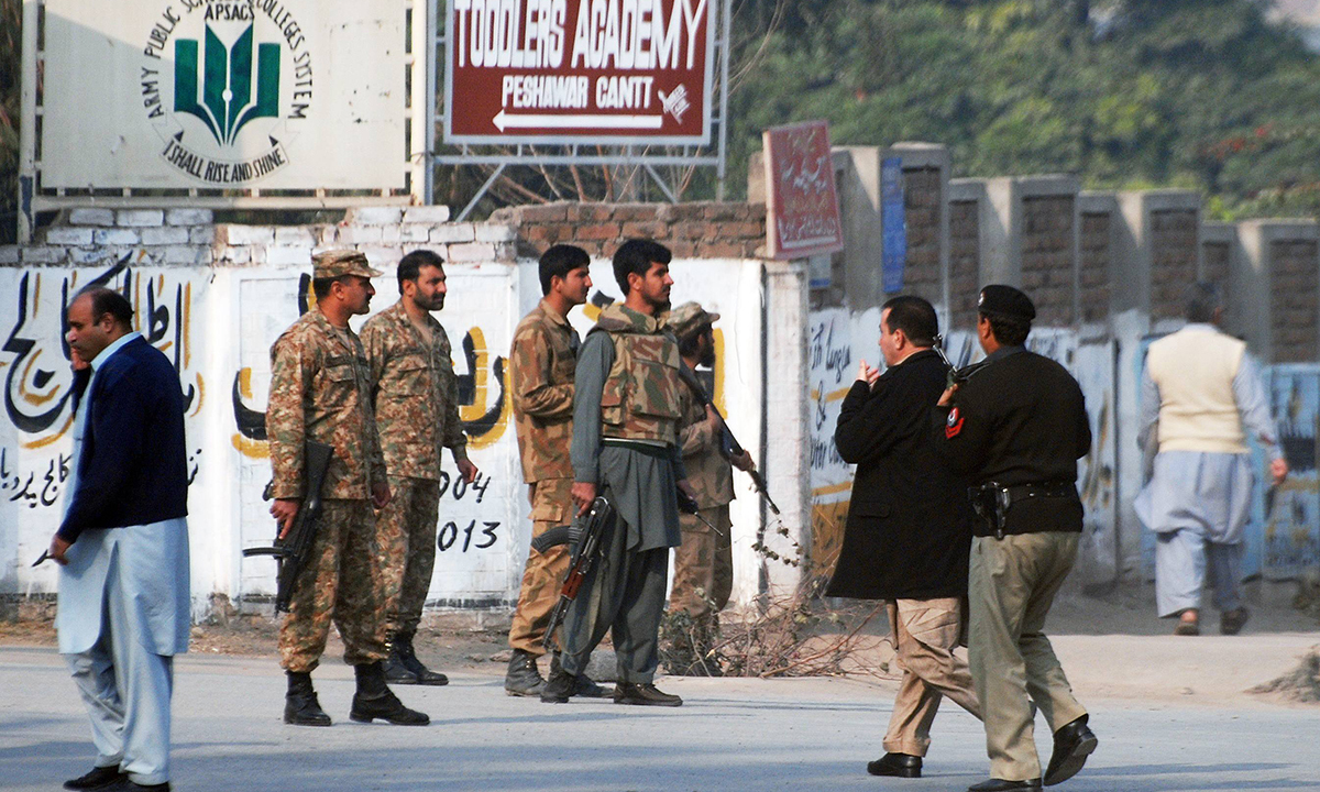 Pakistani security forces takes up a positions on a road leading to the Army Public School that is under attack. — Reuters