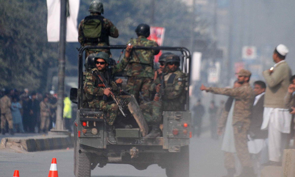 Pakistani security forces drive on a road leading to the Army Public School. — Reuters