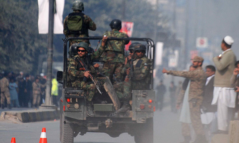 Security forces drive on a road leading to the Army Public School that is under attack by Taliban gunmen in Peshawar - Reuters