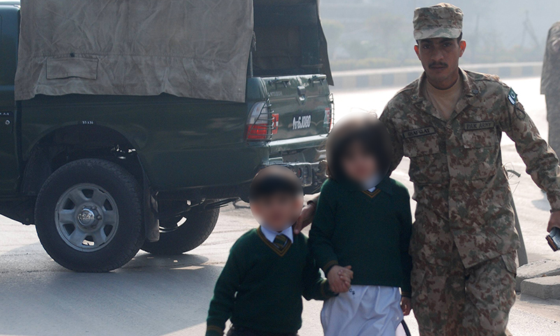 A soldier escorts schoolchildren from the Army Public School that was attacked by TTP gunmen in Peshawar. — Reuters