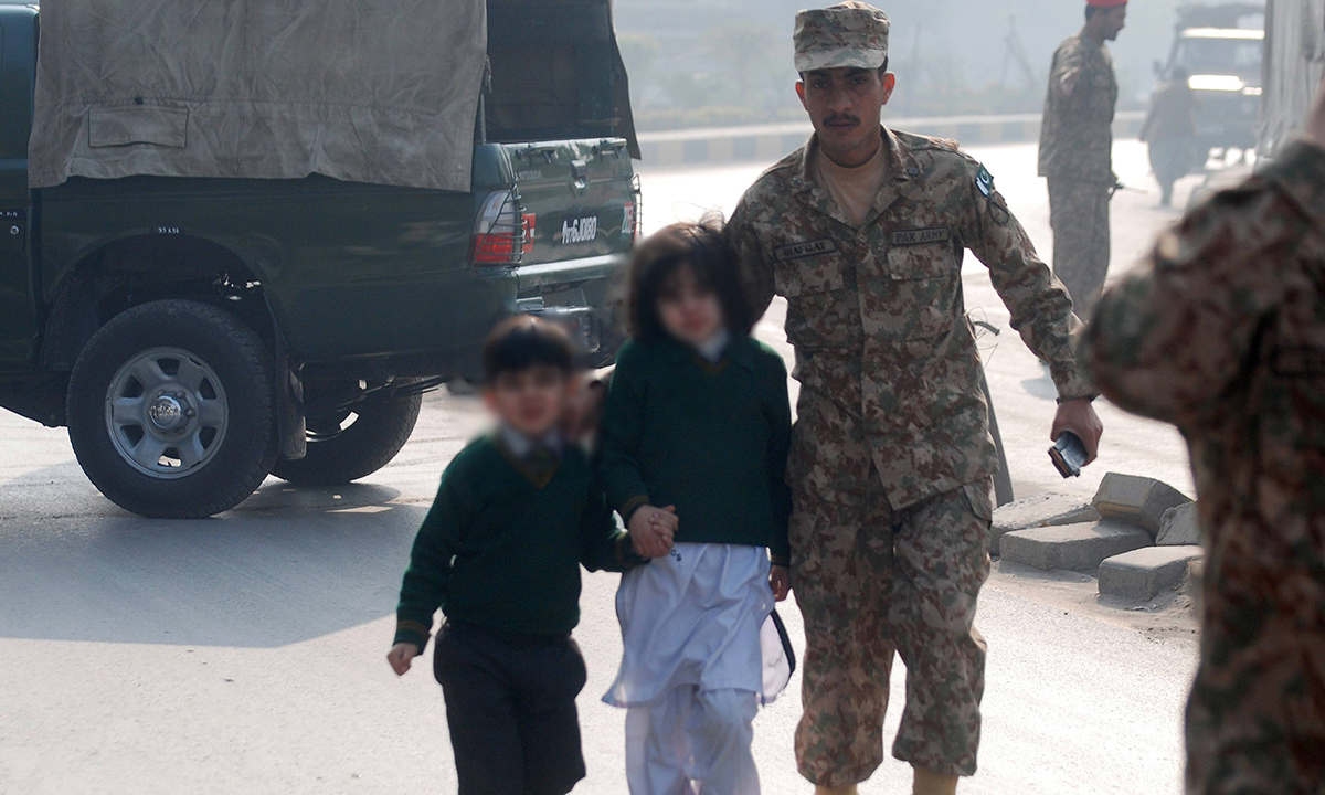 A soldier escorts schoolchildren after they were rescued from the Army Public School. — Reuters