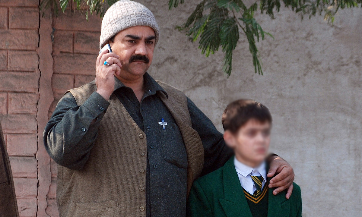 A man talks on a phone, with his arm around a student.— Reuters