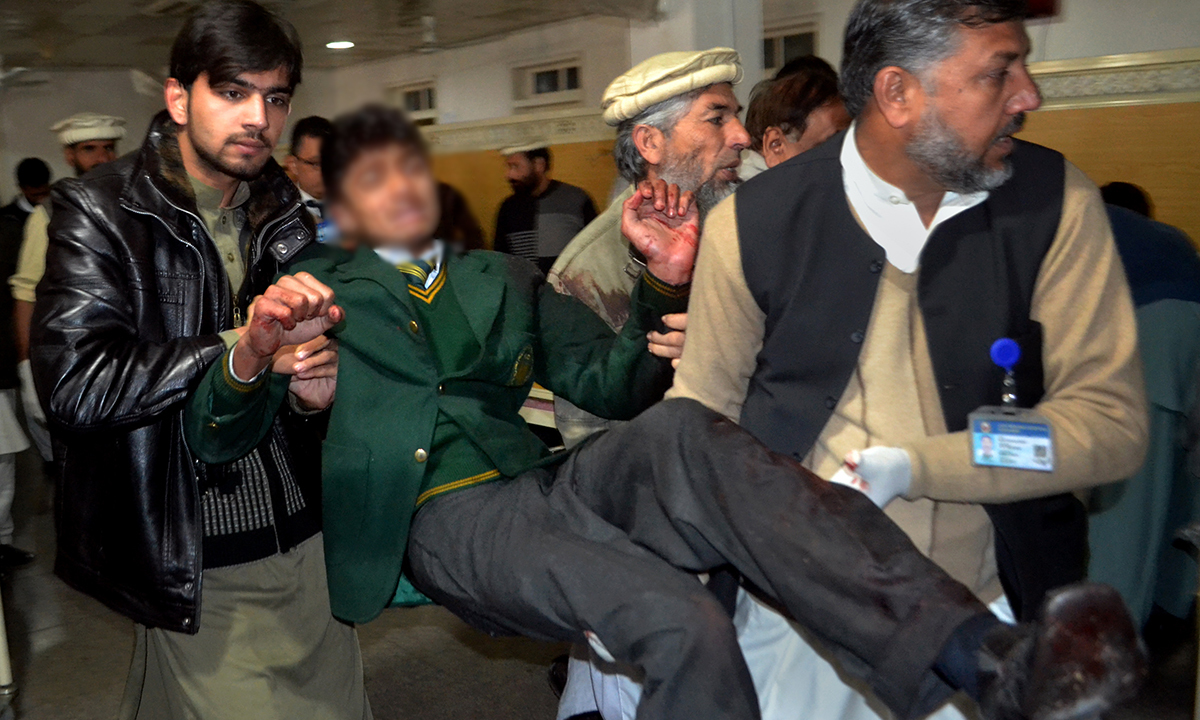 Pakistani volunteers carry a student injured in the shootout. — AP