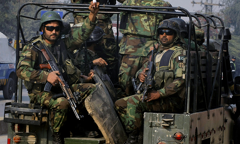Army troops arrive to conduct an operation at a school under attack by terrorists in Peshawar. — AP