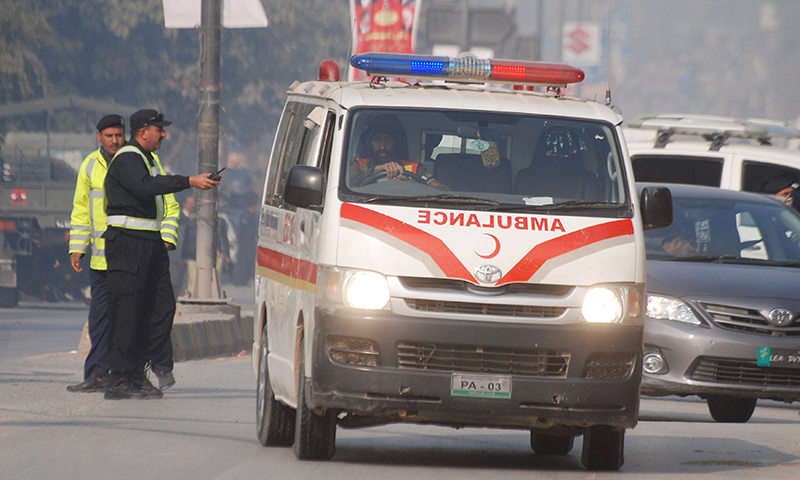 An ambulance drives away from the Army Public School that is under attack by terrorists in Peshawar. — Reuters