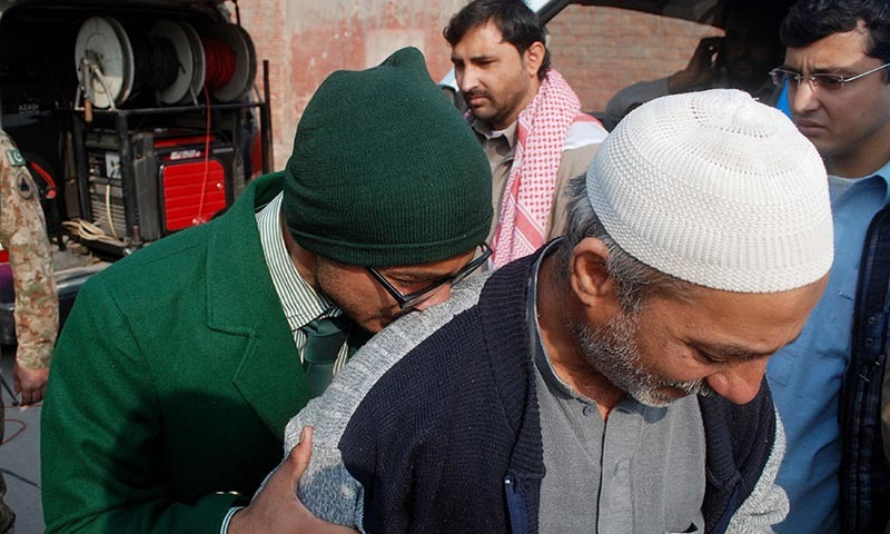 A student cries on a man's shoulder, after he was rescued from the Army Public School - Reuters