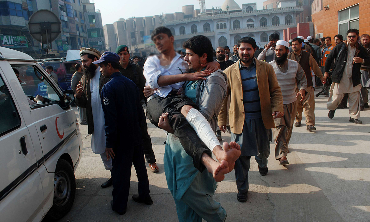 A man carries a student, who was injured during the attack. — Reuters