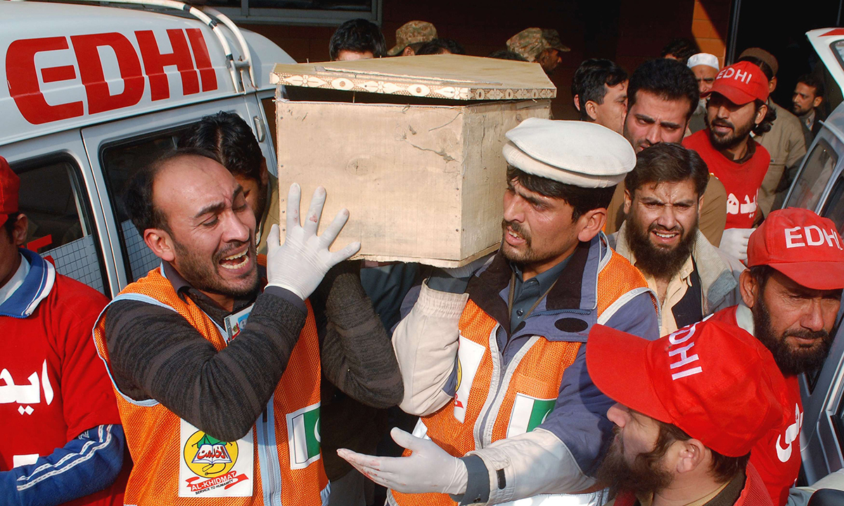 Rescue workers and family members carry the coffin of a student, who was killed during the attack. — Reuters