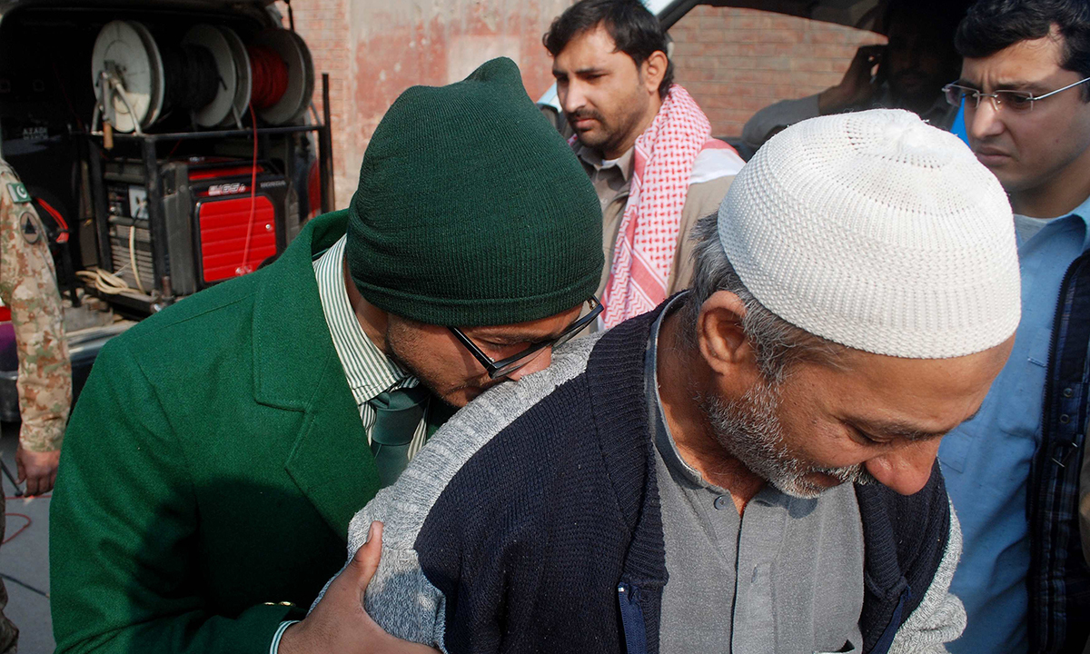 A student cries on a man's shoulder, after he was rescued from the Army Public School.— Reuters