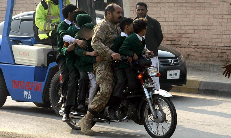 Army personnel shifting the school children on motorbike following the attack on Army Public School situated on Warsak Road. — INP