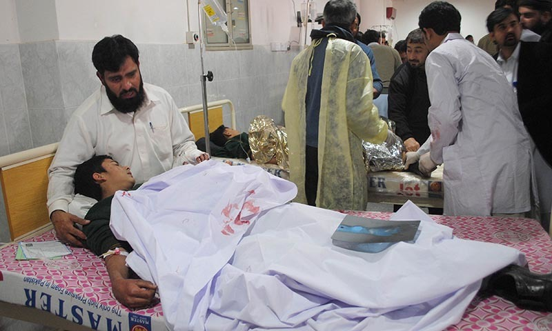 A man comforts his son at Lady Reading Hospital in Peshawar — Reuters